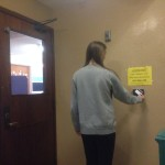 Student uses ID card to enter her residence hall.