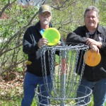 "Graceland University Director of Student Activities, Brad Carr, and Grounds Manager, Bob Kelly, display a basket target where disc golfers will ""putt"" to ""hole out"" on the two disc golf courses in Lamoni during this weekend's tournaments."