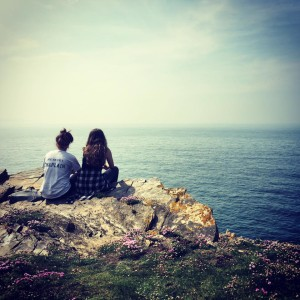 Briana Bendorf and Chelsea SantaLucia sitting at the cliff of the Welsh Coastline.